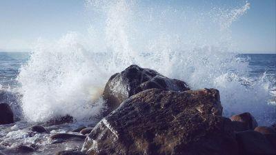ocean splashing against shore line rocks