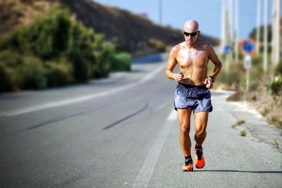 shirtless man jogging wearing sunglasses