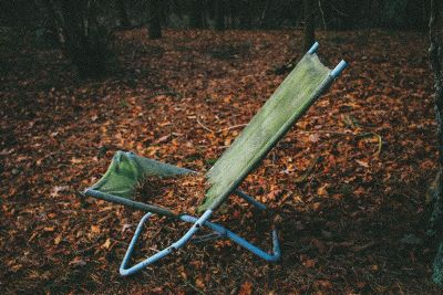 a green lawn chair on top of fall leaves