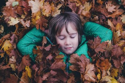 child relaxing in pile of leaves