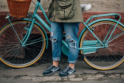 woman ripped jeans with bike
