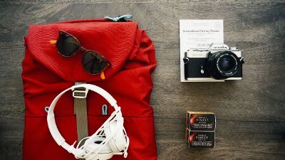 red backpack with camera and headphones