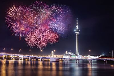 fireworks exploding over bridges and tower