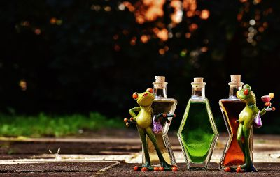 puppet frogs in front of bottles