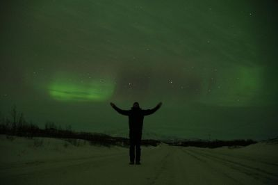 man standing at northern lights