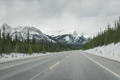 snow capped mountains with highway