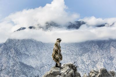 person wrapped in blanket on mountaintop