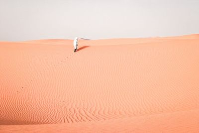 a man walking on pink sand