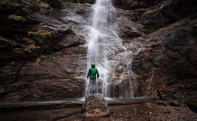 man under waterfalls