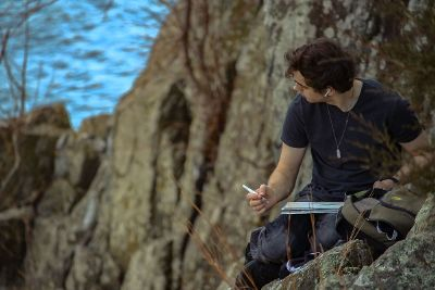 man drawing on cliff