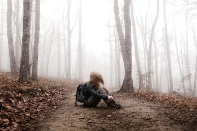 girl sitting in foggy forest