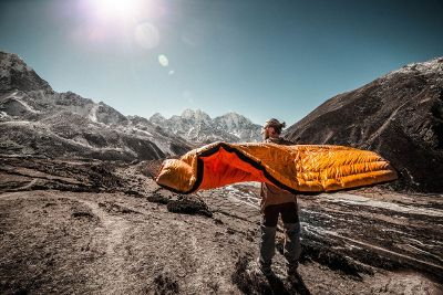 man with sleeping bag in mountains