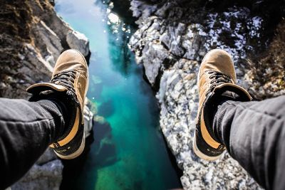 feet hanging over river