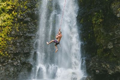man swinging on rope over waterfall