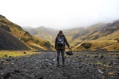 woman walking away toward mountain