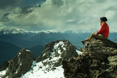 woman sitting on mountaintop