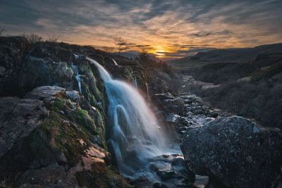 waterfall in a sunset landscape