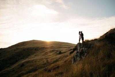 couples kiss on hillside