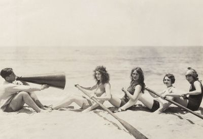 women practicing paddling on beach