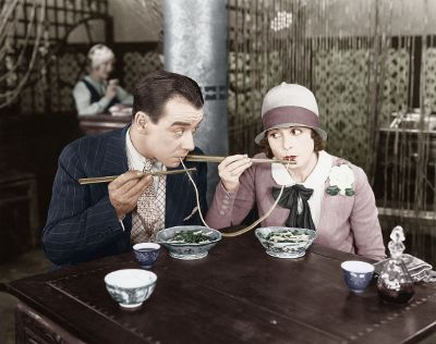man and woman slurping noodle
