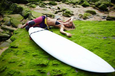 surfer lying alongside her board