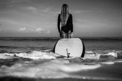 woman carrying surfboard into water