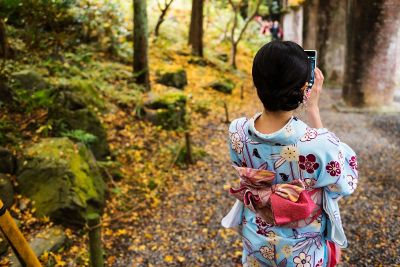 kimonoed woman checks phone in forest