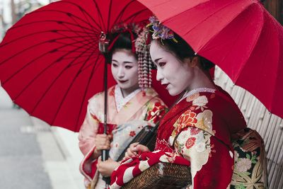 two geisha holding red umbrellas